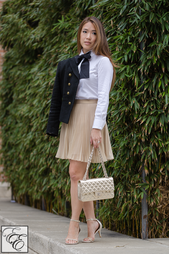 full body shot of karl lagerfeld black neck bow, Banana Republic cropped military jacket, Club Monaco gold pleated a-line skirt, Stuart Weitzman Nudist gold sandals, and Chanel gold bag