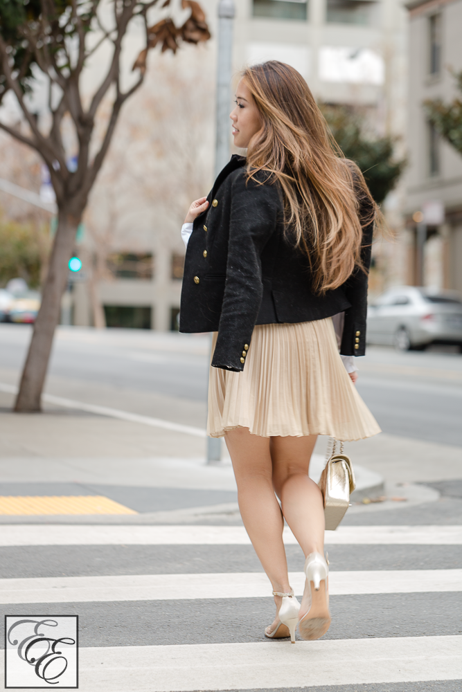 Black and gold winter holiday outfit - black ribbon neck bow, white shirt, cropped military jacket, and pleated gold skirt