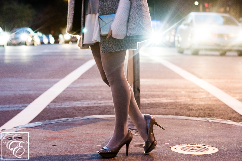 Light grey cape, peplum top, white flared skirt, grey hosiery, arm warmers, and metallic pumps and clutch: close-up of hosiery and heels