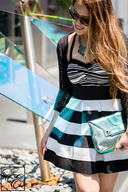 Target swimsuit with black and white flared skirt, black crochet sweater, and metallic turquoise accessories