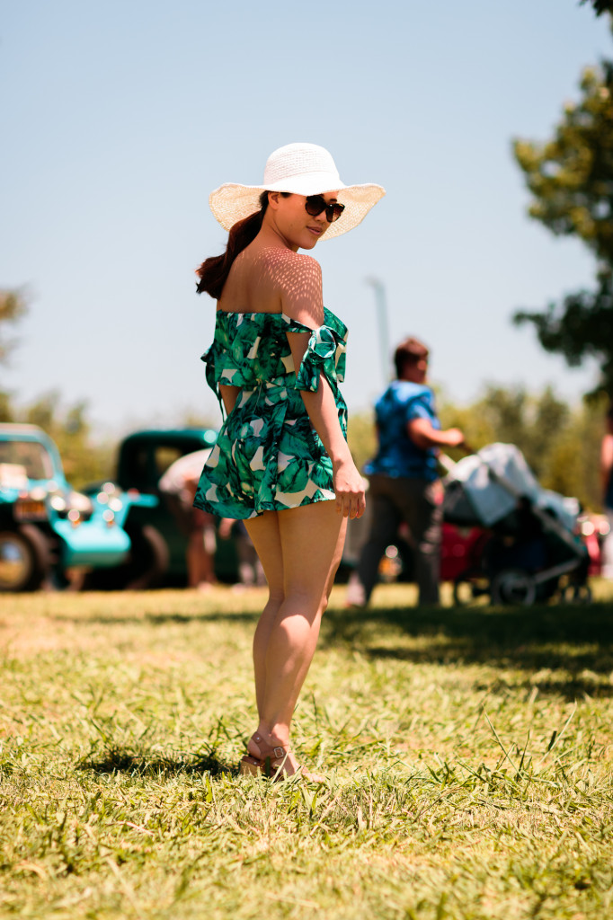 Woman wearing Tobi tropical print romper set (off-shoulder sleeves and shorts) with Hatattack sunhat and Chanel sunglasses